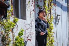 En armenisk kvinna står på hennes hus som flätas ihop med murgrönan och druvor royaltyfri fotografi