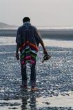En arrière d'un homme marchant sur une plage Photo stock