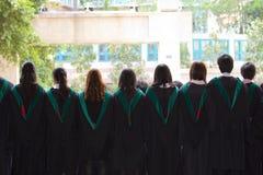 En arrière de l'université reçoit un diplôme avec leurs robes Photographie stock