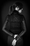 En arrière de la belle fille dans la robe noire au-dessus du noir image libre de droits