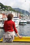 En arrière de la femme s'asseyant sur le quai dans le dock avec des bateaux Photographie stock