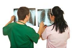 En arrière des médecins contrôlant des rayons X Image libre de droits