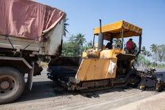 En asfaltmaskin och en lastbil med släpet Royaltyfria Foton