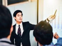 En asiatisk affärsman framlade mötet som förklarar och arkivbild