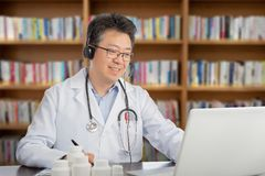 En asiatisk doktor som konsulterar avlägset med en patient Telehealth begrepp arkivfoto