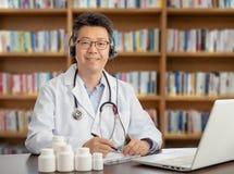 En asiatisk doktor som konsulterar avlägset med en patient Telehealth begrepp royaltyfri foto
