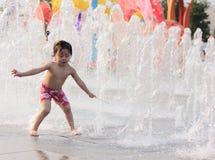 En asiatisk flicka som by leker, bevattnar springbrunnen Arkivfoton