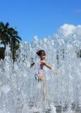 En asiatisk flicka som leker vid vattenspringbrunnen Arkivbilder