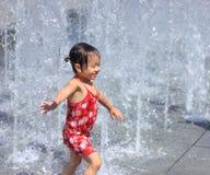 En asiatisk flicka som leker vid vattenspringbrunnen Fotografering för Bildbyråer