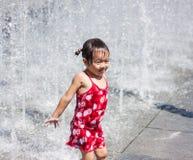 En asiatisk flicka som spelar vid vattenspringbrunnen Royaltyfri Bild