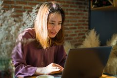 En asiatisk härlig kvinna arbetar i coffee shop arkivbild