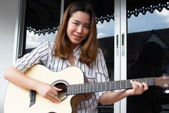 En asiatisk härlig kvinna spelar gitarren royaltyfri foto