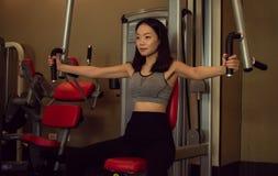 En asiatisk härlig kvinna utbildar i idrottshallen royaltyfri fotografi