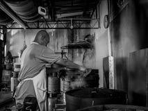 En asiatisk kock gör klimpar i ett restaurangkök Arkivbild