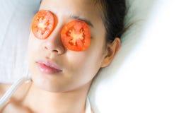 En asiatisk kvinna satte stycken av tomaten på hennes ögon arkivbild