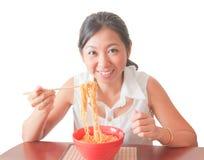 En asiatisk kvinna som äter nudlar Arkivbild