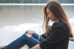 En asiatisk kvinna som bara sitter på en gammal träpir vid floden med mening lycklig, himmel- och bergbakgrund royaltyfri fotografi