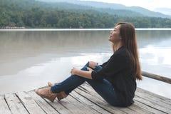 En asiatisk kvinna som bara sitter på en gammal träpir vid floden med mening lycklig, himmel- och bergbakgrund arkivbild