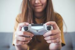 En asiatisk kvinna som rymmer den modiga kontrollanten, medan att spela spelar med känslig gyckel och lyckligt Arkivbild