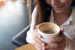 En asiatisk kvinna som rymmer en kaffekopp, innan att dricka med mening bra i kafé arkivbild