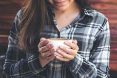 En asiatisk kvinna som rymmer en kaffekopp, innan att dricka med mening bra i kafé fotografering för bildbyråer