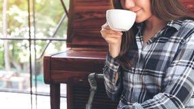 En asiatisk kvinna som rymmer en kaffekopp, innan att dricka med mening bra i kafé arkivfoton