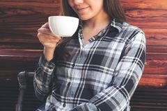 En asiatisk kvinna som rymmer en kaffekopp, innan att dricka med mening bra i kafé royaltyfri foto