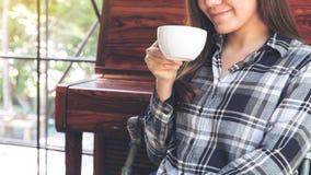 En asiatisk kvinna som rymmer en kaffekopp, innan att dricka med mening bra i kafé arkivbilder