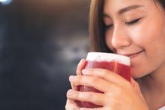En asiatisk kvinna tycker om att dricka jordgubbesodavatten med mening lycklig fotografering för bildbyråer