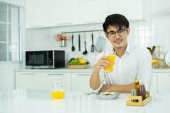 En asiatisk man dricker orange fruktsaft i köket royaltyfri foto