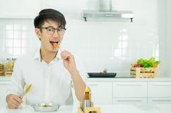 En asiatisk man har frukosten i morgonen arkivfoto