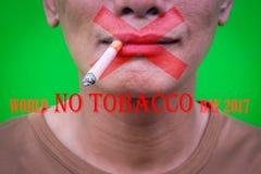 En asiatisk man som röker på grön bakgrund med text`-världen ingen tobakdag2017 `, Arkivbild