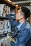 En asiatisk manläsning i ett arkiv Arkivfoto