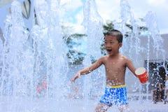 En asiatisk unge som leker i vattenspringbrunn i sommar Arkivfoto