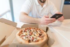 En ask av aptitretande pizza är på tabellen En man använder en telefon på bakgrunden av en öppen ask av smaklig pizza Arkivfoton
