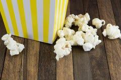 En ask av popcorn på träbakgrund royaltyfri fotografi