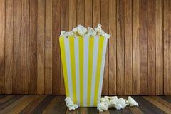 En ask av popcorn på träbakgrund arkivbild
