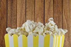 En ask av popcorn på träbakgrund royaltyfri bild