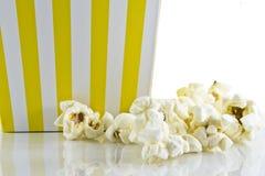 En ask av popcorn på vit bakgrund royaltyfri bild
