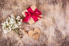 En ask med en gåva, blommor och hjärta En ask med en pilbåge på en träbakgrund Festligt begrepp Royaltyfri Foto