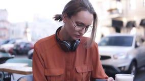En attraktiv blond flicka med hår i en packe och exponeringsglas sitter i ett kafé på gatan, bredvid henne på lager videofilmer