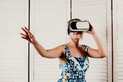 En attraktiv blond kvinna som bär VR-exponeringsglas, rörande somethin royaltyfri foto
