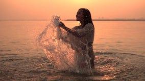 En attraktiv flicka gör att plaska henne händer som står i vattnet mot bakgrunden av solen som har ett bra lynne lager videofilmer