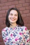 En attraktiv flicka som ler mot bakgrunden av en tegelstenvägg royaltyfri bild