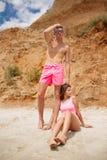 En attraktiv kamrat står nära en härlig flicka i en rosa baddräkt på en strand på en naturlig suddig bakgrund arkivbild