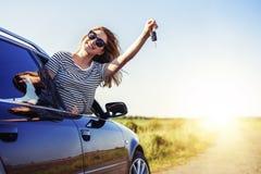 En attraktiv kvinna i en bil rymmer en biltangent i hennes hand royaltyfri fotografi