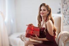 En attraktiv kvinna i ett öppet, den burgundy klänningen som sitter i en chic stol, i ett ljust hem- rum, öppnar en gåva royaltyfria bilder