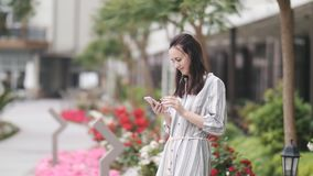 En attraktiv kvinna i en lång klänning och att använda en smartphone på gatan utanför stock video