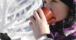En attraktiv kvinna i vinterlag som utomhus dricker kaffe från en råna stock video