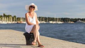 En attraktiv kvinna som bär en sommarhatt på stranden Arkivbilder